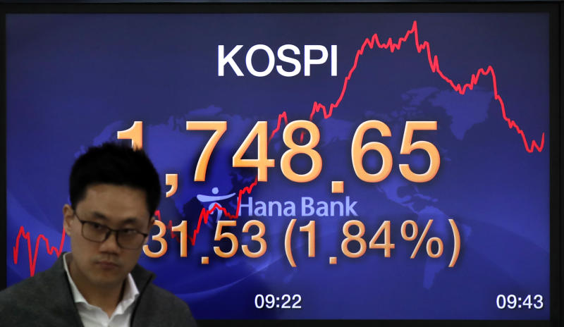 A currency trader walks by the screen showing the Korea Composite Stock Price Index (KOSPI) at the foreign exchange dealing room in Seoul, South Korea, Tuesday, March 31, 2020. Asian shares surged Tuesday after a rally in U.S. stocks, mostly spurred by health care companies' announcements of developments that could aid in the coronavirus outbreak.(AP Photo/Lee Jin-man)