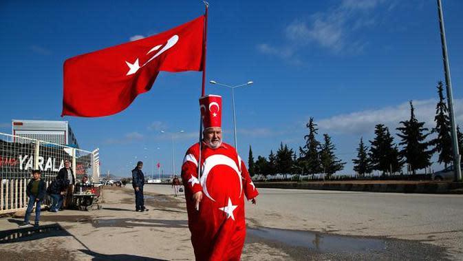 Isikli Tosun Baba (60) memegang dan mengenakan bendera Turki di Oncupinar, Kilis, Turki, Minggu (28/1). (AP Photo/Lefteris Pitarakis)