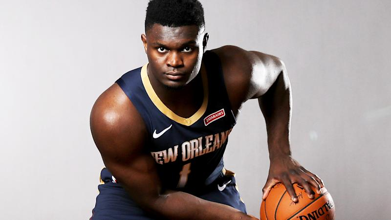 Zion Williams posing with a basketball looking at the camera wearing New Orleans kit.