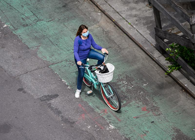 NEW YORK, NEW YORK - MAY 17: A person wears a protective face mask while riding a bicycle in Kips Bay during the coronavirus pandemic on May 17, 2020 in New York City. COVID-19 has spread to most countries around the world, claiming over 316,000 lives with over 4.8 million infections reported. (Photo by Noam Galai/Getty Images)