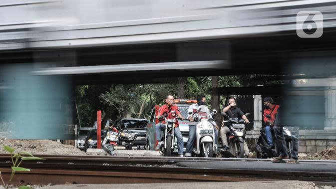 Pengendara motor menunggu kereta melintas saat akan melewati perlintasan sebidang tanpa palang pintu di kawasan TPU Tanah Kusir, Jakarta, Kamis (17/9/2020). Sebelumnya pada Kamis (17/9) pagi terjadi kecelakaan sebuah mobil dan KRL di perlintasan tersebut. (merdeka.com/Iqbal S. Nugroho)