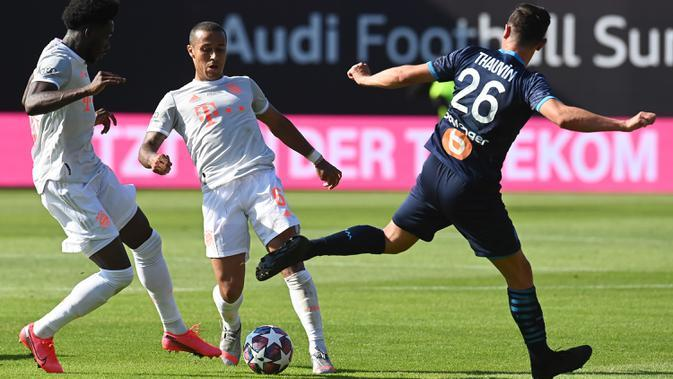 Gelandang Bayern Munchen, Thiago Alcantara dan Alphonso Davies berebut bola dengan penyerang Marseille, Florian Thauvin, pada laga persahabatan di Allianz Arena, Sabtu (1/8/2020) dini hari WIB. Bayern Munchen menang 1-0 atas Marseille. (AFP/Christof Stache/various sources)