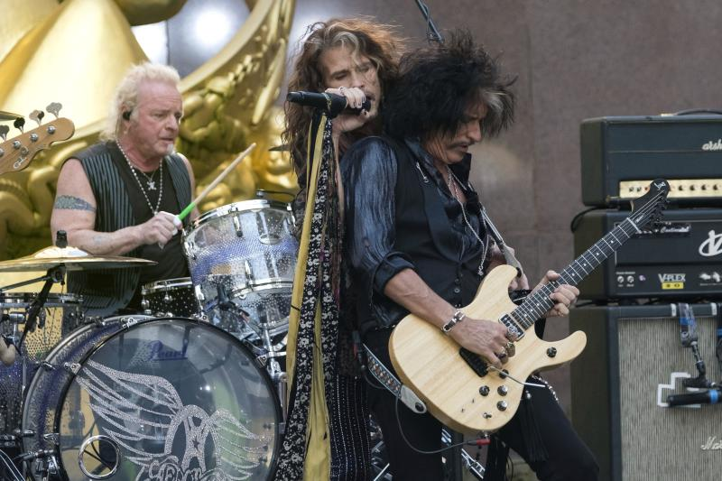 """FILE - In this Aug. 15, 2018, file photo, Joey Kramer, from left, Steven Tyler and Joe Perry of Aerosmith perform on NBC's """"Today"""" show at Rockefeller Center in New York. Kramer, a founding member of the band, filed a lawsuit against his band mates in January 2020 in Massachusetts Superior Court in Boston, claiming he has been kept out of the band after he hurt his ankle in 2019 and missed some shows. The suit comes just as the band is set to perform and be honored at Grammy Awards events. (Photo by Charles Sykes/Invision/AP, File)"""