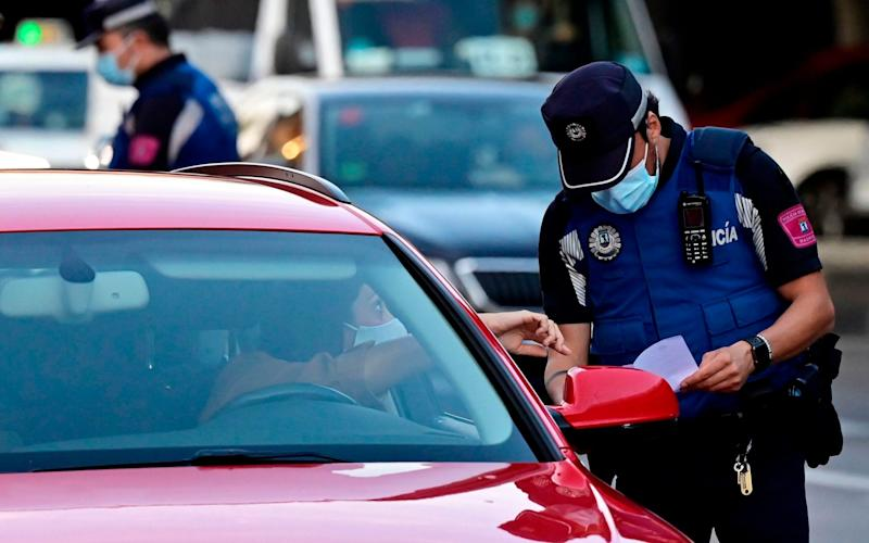 Local police control people's movement in a traffic checkpoint at the Puente de Vallecas neighbourhood, under partial lockdown, in Madrid, on September 21, 2020. - Pierre-Philippe Marcou/AFP