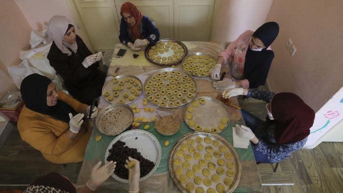 Sejumlah perempuan mengenakan sarung tangan dan masker saat membuat biskuit tradisional jelang Hari Raya Idul Fitri di Kota Tua Hebron, Tepi Barat, Palestina, Selasa (19/5/2020). Biskuit tradisional akan dijual secara online karena pandemi virus corona COVID-19. (HAZEM BADER/AFP)