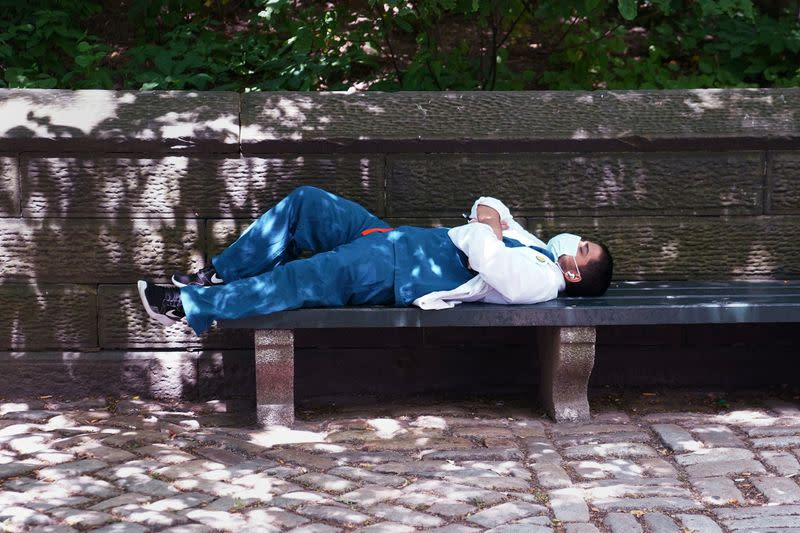 A medical professional takes a nap on a park bench in the Manhattan borough of New York City