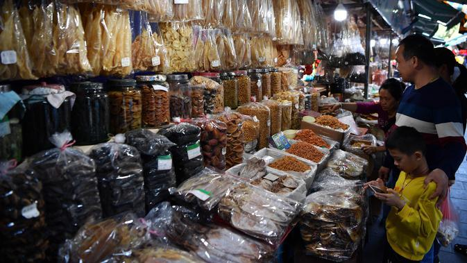 Calon pembeli memilih makanan laut kering di sebuah pasar di Kota Haikou, Provinsi Hainan, China, Rabu (15/1/2020). Warga Haikou akhir-akhir ini sibuk berbelanja untuk menyambut Tahun Baru Imlek 2020. (Xinhua/Guo Cheng)