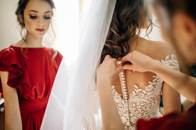 Bridesmaid in a red dress as a man cuttons up back of bride's dress