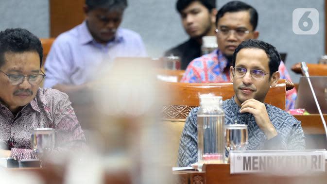 Menteri Pendidikan dan Kebudayaan (Mendikbud), Nadiem Makarim (kanan) mengikuti rapat kerja dengan Komisi X DPR di Kompleks Parlemen Senayan, Jakarta, Rabu (6/11/2019). Nadiem Makarim menghadiri rapat perdana dengan Komisi X DPR RI. (Liputan6.com/Johan Tallo)