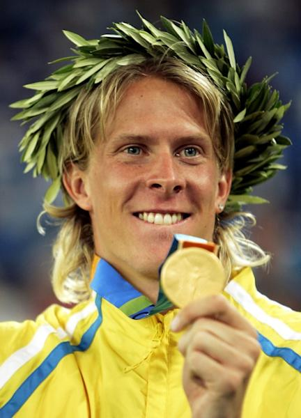 FILE PHOTO: Sweden's Olsson shows his gold medal for the men's triple jump at the Athens 2004 Olympic Games.