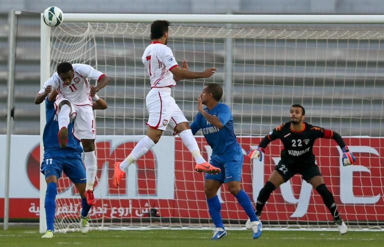 Ahmad Khalil (L front) of United Arab Emirates vies for the ball against Fahed al-Ibrahim (back) during the two teams' semi final match in the 21st Gulf Cup in Manama, on January 15, 2013. AFP PHOTO/MARWAN NAAMANI