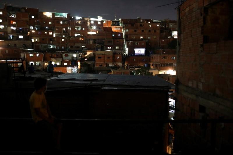 A boy watches a movie projected on a giant screen in the low-income neighborhood of Petare, amid the coronavirus disease (COVID-19) outbreak in Caracas