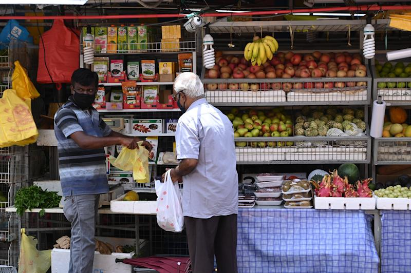 A vendor wearing a protective facemask amid fears about the spread of the COVID-19 coronavirus serves a customer at a fruit stall in Singapore on May 8, 2020. (Photo by ROSLAN RAHMAN / AFP) (Photo by ROSLAN RAHMAN/AFP via Getty Images)