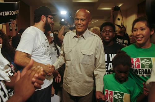American singer, songwriter, actor and social activist Harry Belafonte, Jr. greets Dream Defenders and PowerUCenter members as he heads to Florida Gov. Rick Scott's office Friday July 26, 2013 in the Capitol in Tallahassee, Fla. Dream Defenders were joined by Belafonte, Jr. as they went into their 11th day of a sit-in of Florida Gov. Rick Scott's office. The sit-in is their response to the 'not guilty' verdict in the trial of George Zimmerman, the Florida neighborhood watch volunteer who fatally shot Trayvon Martin. They are continuing to demand Scott call a special session. (AP Photo/Phil Sears)