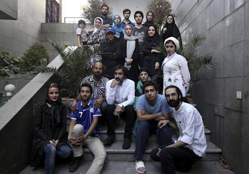 """Iranian theater director Amin Miri, third from left in second row, poses with his theater group prior to their performance of """"The Blue Feeling of Death,'' outside the theater hall in Arasbaran Cultural Center in Tehran, Iran, Thursday, July 18, 2013. The production opened last month as a showcase of activist art against Iran's legal codes that allow death sentences for children _ who then wait until their 18th birthday for possible execution. Opening night came even as Iranian officials tightened controls on the social media and other forms of political opposition before presidential elections, whose centrist winner, Hasan Rouhani, has brought hope of reversing some of the crackdowns. (AP Photo/Vahid Salemi)"""