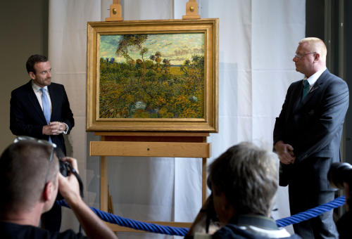 "CAPTION CORRECTION, CORRECTS SPELLING OF SURNAME TO REFLECT AP STYLE - Photographers take pictures as Van Gogh Museum director Axel Rueger, left, and a security guard, right, stand next to newly discovered ""Sunset at Montmajour"" after unveiling the painting by Dutch painter Vincent van Gogh during a press conference at the museum in Amsterdam, Netherlands, Monday, Sept. 9, 2013. The museum has identified the long-lost painting which was painted by the Dutch mater in 1888, the discovery is the first full size canvas that has been found since 1928 and will be on display from Sept. 24. (AP Photo/Peter Dejong)"