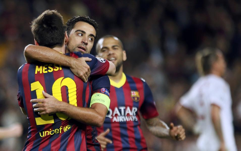 Barcelona's Messi is congratulated by team mates Xavi and Alves after scoring his second goal against AC Milan during their Champions League soccer match in Barcelona