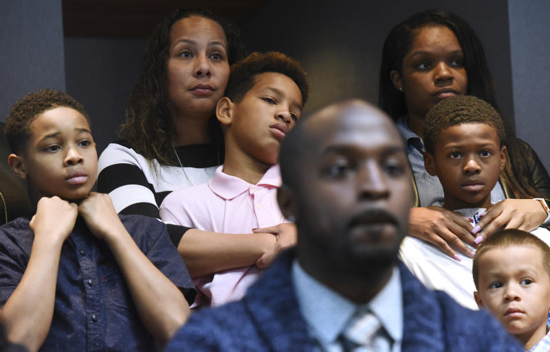 Marcus Riley of Bolingbrook, Ill., foreground, speaks during a press conference Tuesday, Nov. 5, 2019 in Aurora, Ill., about how he and other families, background, were asked to move because others didn't want to sit by them at a Naperville, Ill., Buffalo Wild Wings restaurant. (Paul Valade/Daily Herald via AP)