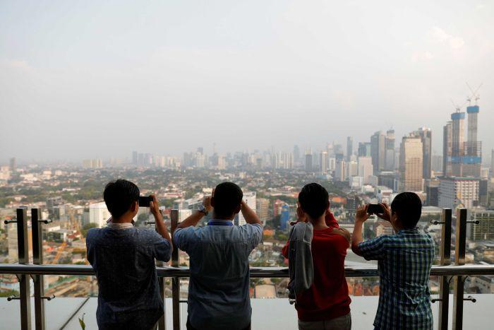 A row of men taking photos of a smoggy Jakarta skyline