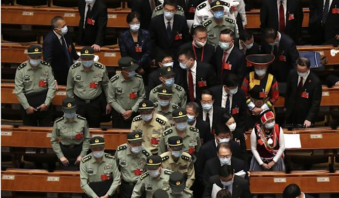 Military delegates leave after the opening session of the National People's Congress at the Great Hall of the People in Beijing on Friday. Photo: AP