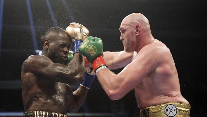 Tyson Fury (kanan) melepaskan pukulan ke arah wajah Deontay Wilder dalam pertarungan tinju kelas berat WBC di Staples Center, Los Angeles, Minggu (2/12/2018) pagi WIB. (Foto AP / Mark J. Terrill)