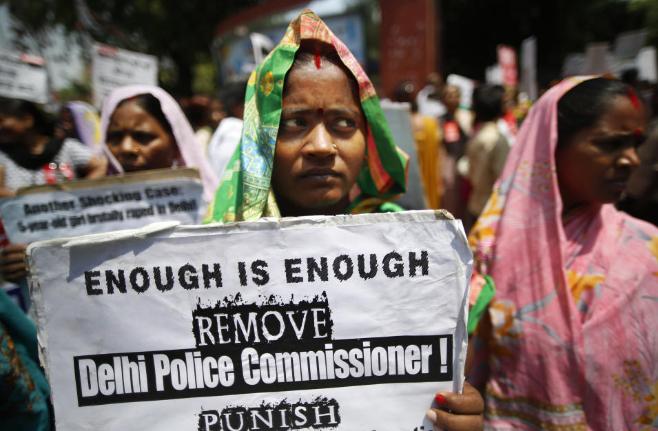 An Indian woman holds a poster as she protests with others against how Indian authorities handle sex crimes near the Parliament in New Delhi, India, Monday, April 22, 2013 after a second suspect was arrested in the rape of a 5-year-old girl. Child rights activists say the rape last week of the girl is just the latest case in which Indian police failed to take urgent action on a report of a missing child. Three days after the attack, the girl was found alone in locked room in the same New Delhi building where her family lives. (AP Photo/ Saurabh Das)