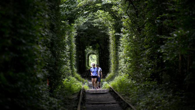 Seorang wanita dan pria berjalan di sepanjang bekas rel kereta api atau disebut 'Tunnel of Love' dekat desa Ukraina Klevan, Rivno, (6/8). Terowongan ini menjadi tempat bagi wisatawan dan pasangan yang sedang jatuh cinta. (AFP Photo/Sergei Supinsky)