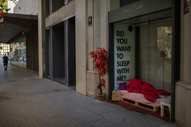 Reduan Elhammoudani, 45, from Syria, sleeps in a hotel entrance, closed during the coronavirus outbreak in Barcelona, Spain, Saturday, June 6, 2020. Reduan fled Syria seven years ago, after his wife and two children, 3 and 7, were killed in a bombing during the war. Since the confinement began due to the coronavirus outbreak, Reduan has subsisted thanks to the charity of the neighbourhood residents. (AP Photo/Emilio Morenatti)