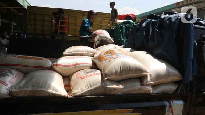 Buruh memenidahkan karung beras di pasar induk beras Cipinang, Jakarta, Sabtu (16/5/2020). mengantisipasi penyebaran Covid-19 sejumlah kuli dan buruh di Pasar Induk beras Cipinang diberi obat herbal mentah untuk meredakan panas. (Liputan6.com/Herman Zakharia)