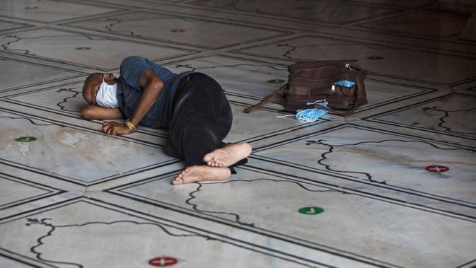Seorang penjual masker beristirahat di lantai Masjid Jama yang dibuka kembali setelah pemerintah melonggarkan lockdown di kawasan Kota Tua Delhi, Selasa (7/7/2020). India pada 6 Juli menjadi negara dengan jumlah virus corona tertinggi ketiga di dunia. (Photo by XAVIER GALIANA / AFP)