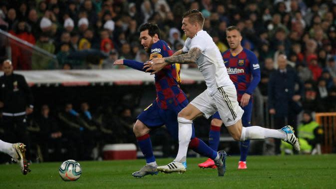 Megabintang Barcelona, Lionel Messi, berebut bola dengan pemain Real Madrid, Toni Kroos pada lanjutan pertandingan La Liga di Santiago Bernabeu, Minggu (2/3/2020). Real Madrid membungkam Barcelona 2-0 dan merebut puncak klasemen dari Barcelona. (AP/Andrea Comas)