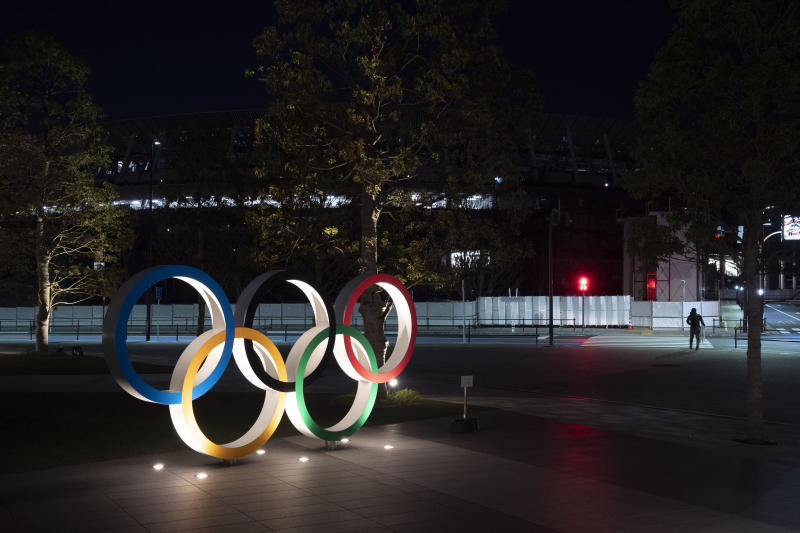 "The Olympic rings stand near the New National Stadium in Tokyo, Tuesday, March 24, 2020. IOC President Thomas Bach has agreed ""100%"" to a proposal of postponing the Tokyo Olympics for about one year until 2021 because of the coronavirus outbreak, Japanese Prime Minister Shinzo Abe said Tuesday. (AP Photo/Jae C. Hong)"