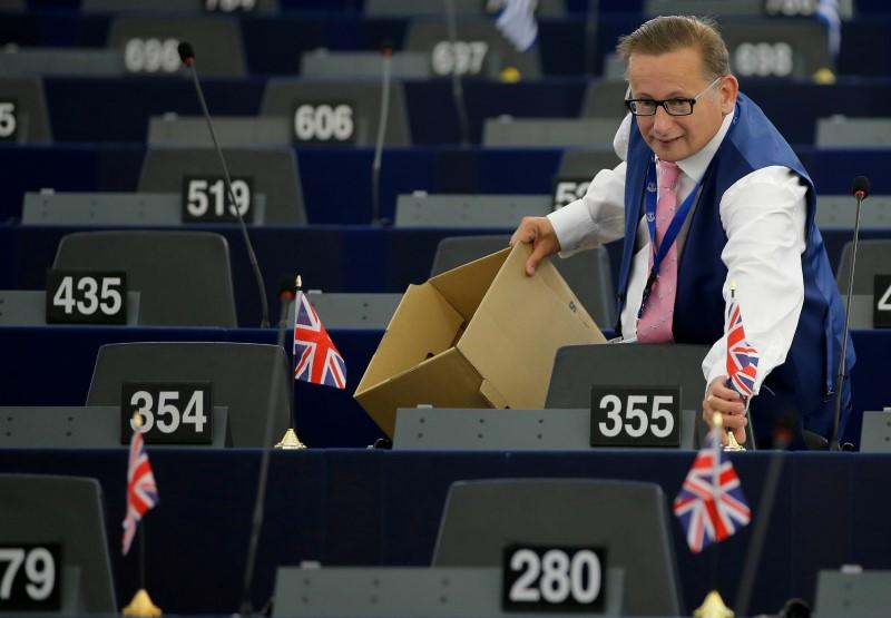 FILE PHOTO: UKIP member Finch puts British Union Jack flags on the desks of fellow members of the Europe of Freedom and Direct Democracy Group of the European Parliament, ahead of a debate in Strasbourg