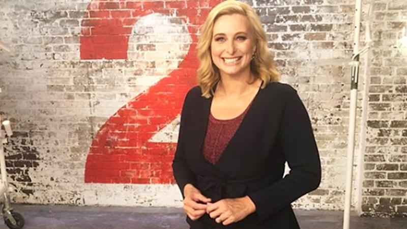 A photo of host Joh Griggs wearing a black blazer jacket and red top on set of House Rules.