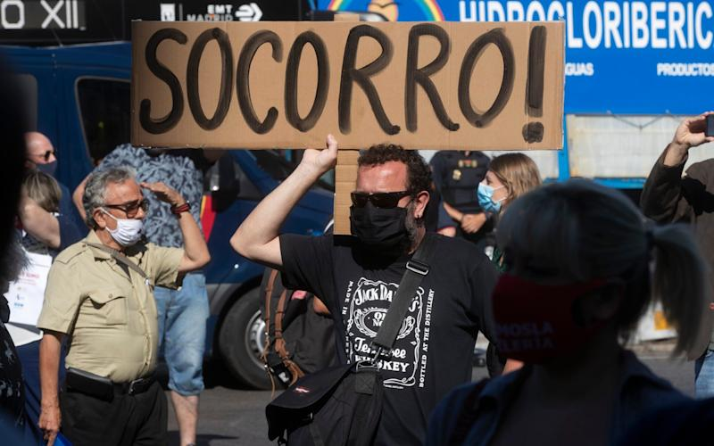 A man holds a sign reading Help! as bar and restaurant owners and workers protest against Covid-19 restrictions in Madrid - AP Photo/Paul White