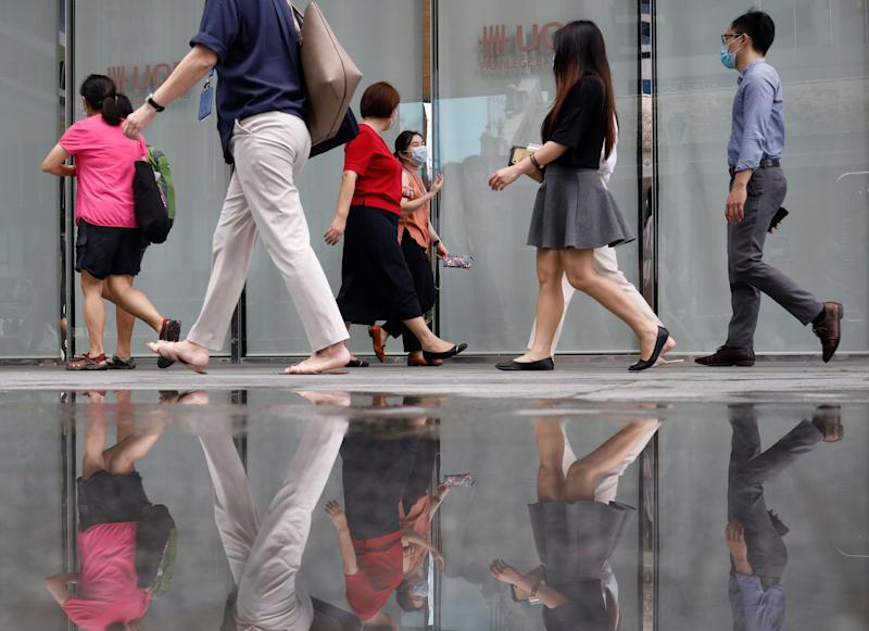 Office workers wearing protective face masks walk in Singapore's central business district, during the coronavirus disease (COVID-19) outbreak in Singapore, August 17, 2020. REUTERS/Edgar Su