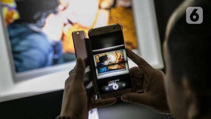 Pengunjung mengambil gambar pada pameran Satu Dekade Haul Presiden ke IV Republik Indonesia KH Abdurrahman Wahid atau Gus Dur di Kantor DPP PKB, Jakarta, Rabu (15/1/2020). Pameran sekaligus lomba foto ini diikuti oleh puluhan fotografer dari seluruh Indonesia. (Liputan6.com/Faizal Fanani)