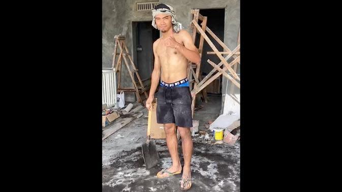 Bek Madura United, Andik Rendika Rama, beraktivitas menjadi kuli bangunan selama pandemi virus corona berlangsung. (Bola.com/Aditya Wany)
