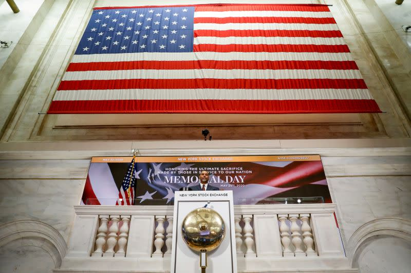 FILE PHOTO: A staff member rings closing bell in honor of Memorial Day and the lives lost in military service to the U.S., as preparations are made for the return to trading, on the floor at the NYSE in New York