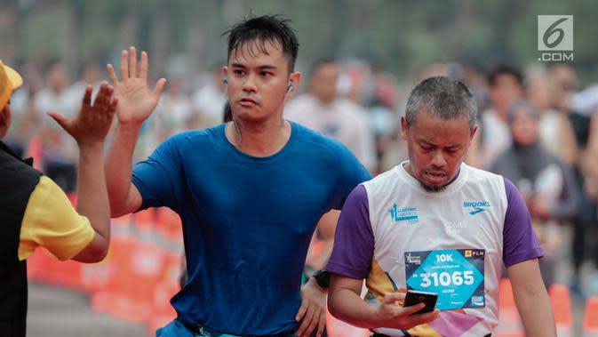 Ekspresi sejumlah pelari saat mencapai garis finis Jakarta Marathon 2018 di Gelora Bung Karno, Jakarta, Minggu (28/10). 12.500 pelari meramaikan Jakarta Marathon 2018 yang di sponsori PLN. (Liputan6.com/Faizal Fanani)