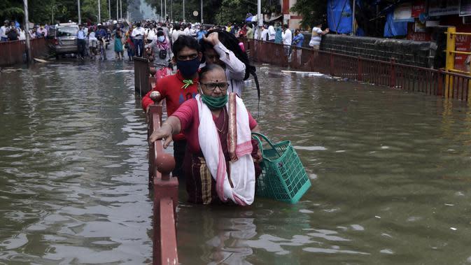 Orang-orang berjalan melewati jalan yang tergenang air setelah hujan lebat di Mumbai, India, Rabu (23/9/2020). Musim hujan di India berlangsung dari Juni hingga September. (AP Photo/Rajanish Kakade)