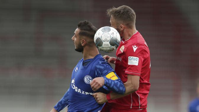 Pemain Union Berlin, Florian Huebner, berebut bola dengan pemain Schalke, Ahmed Kutucu, pada laga Bundesliga di Weserstadion Minggu (7/6/2020). Kedua tim bermain imbang 1-1. (AP/Michael Sohn)