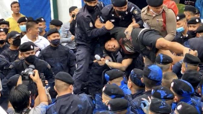 Polisi menahan seorang pemuda dalam unjuk rasa di Thailand (@ThaiEnquirer/Twitter).
