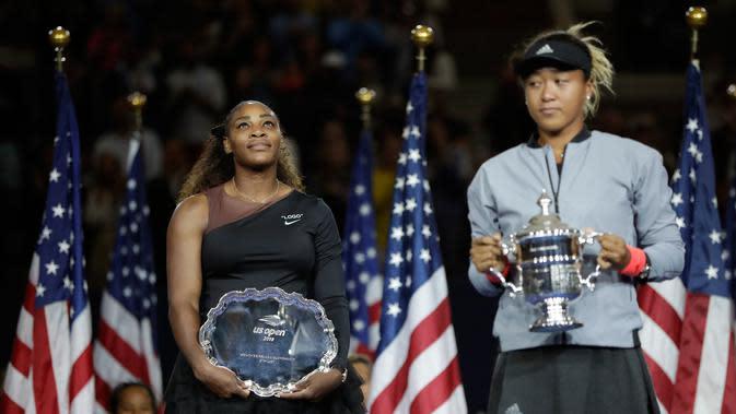 Petenis AS, Serena Williams melihat petenis Jepang, Naomi Osaka saat memegang trofi turnamen AS Terbuka seusai memenangi partai final di Arthur Ashe Stadium, New York, Sabtu (8/9). Naomi Osaka menang dua set dengan skor 6-2 dan 6-4. (AP/Julio Cortez)
