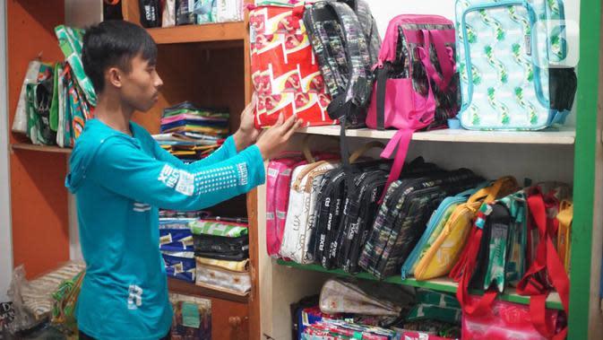 Pekerja menata tas dari sampah plastik yang diproduksi di kawasan Pasar Minggu, Jakarta, Senin (13/1/2020). Rumah daur ulang plastik itu memproduksi barang dari limbah plastik seperti tas, payung, dompet dan koper dengan harga jual berkisar Rp20.000 hingga Rp700.000. (Liputan6.com/Immanuel Antonius)