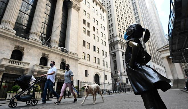 The Fearless Girl statue, now masked, overlooking the New York Stock Exchange. Photo: AFP