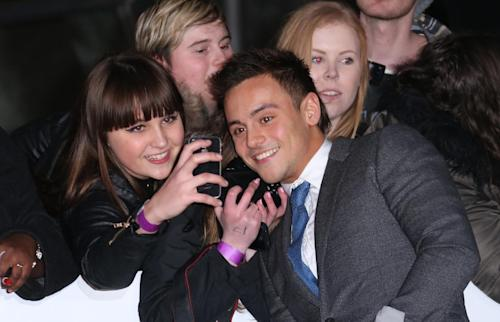 British diver Tom Daley interacts with fans upon arrival at the BRIT Awards 2014 at the O2 Arena in London on Wednesday, Feb. 19, 2014. (Photo by Joel Ryan/Invision/AP)