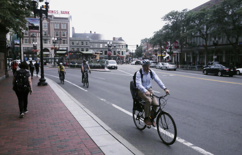 FILE - In this Aug. 13, 2019, file photo, a bicyclist rides on a bike lane through Harvard Square in Cambridge, Mass. A government agency is recommending that all 50 states enact laws requiring bicyclists to wear helmets to stem an increase in bicycle deaths on U.S. roadways. The recommendation was among several issued by the National Transportation Safety Board after a hearing Tuesday, Nov. 5, on bicycle safety. (AP Photo/Charles Krupa, File)