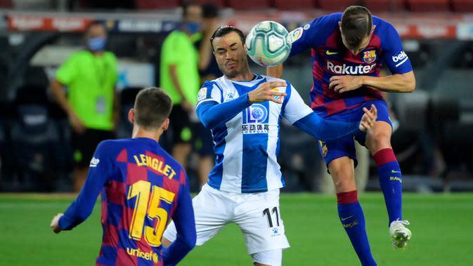 Pemain Espanyol, Javier Puado (kiri) berebut bola dengan bek Barcelona, Jordi Alba pada lanjutan pertandingan La Liga Spanyol di Camp Nou, Kamis (9/7/2020) dini hari WIB. Barcelona menang tipis 1-0 atas Espanyol lewat gol yang dicetak Luis Suarez. (LLUIS GENE / AFP)