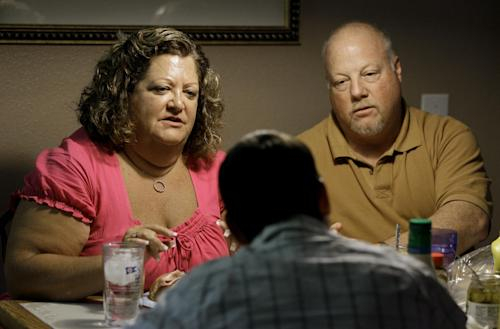 In this July 10, 2011 photo, Deb Carlson, left, and her husband Doug, right, have lunch with their adopted sons in Valrico, Fla. The Carlsons' adopted sons have trashed bedrooms, stolen credit cards and threatened to kill them, one drew a disturbing pictures of throwing a party after beheading the southwest Florida couple. While the overwhelming majority of adoptions end happily, some families like the Carlsons say they weren't told about their new child's psychological problems and can't get help from the government agencies that recruited them. (AP Photo/Chris O'Meara)
